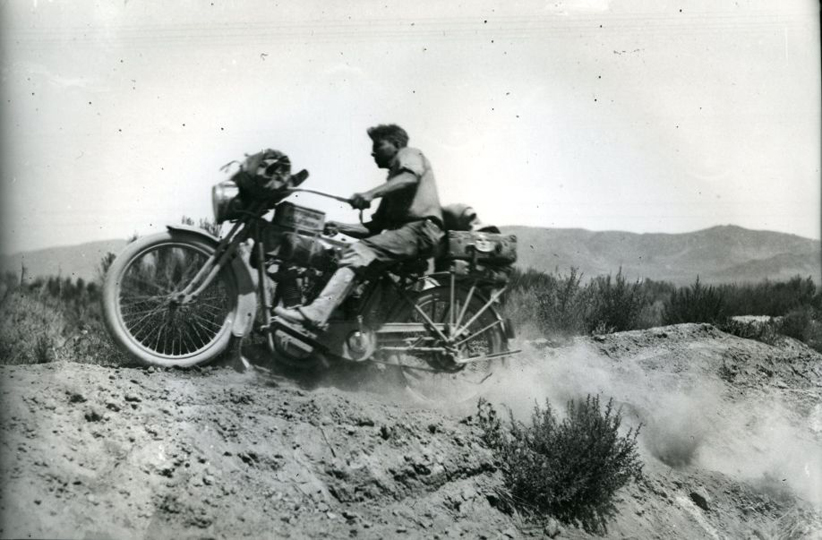 Riding motorbike in desert 1915 - climbing bank (Laing)